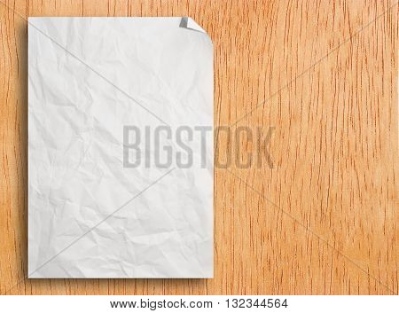 Crumpled white template paper on brown wood texture for design