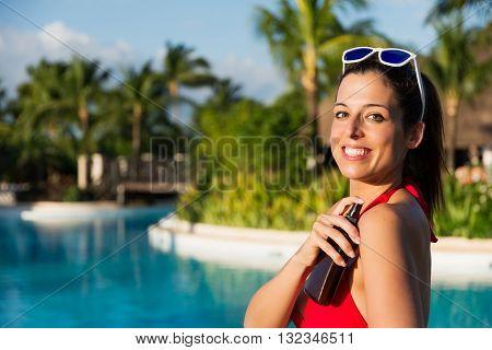 Woman On Summer Vacation Using Suntan Lotion Bottle