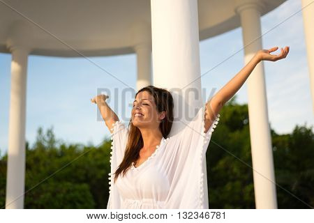 Blissful woman enjoying relax and freedom on vacation. Brunette female raising arms. Happiness and leisure on summer holidays.