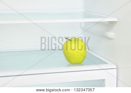 Lifestyle concept.Yellow apple in domestic refrigerator taken closeup.Toned image.