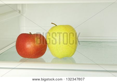 Healthy lifestyle.Red and yellow apple in domestic refrigerator taken closeup. Toned image.