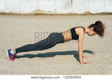 Young Athletic Woman In Sportswear Doing Push-ups On The Sand On A Sunny Morning