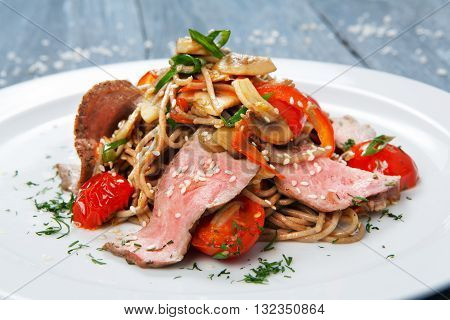 Asian food. Whole grain brown vermicelli noodles with mushrooms, vegetables, sun-dried tomatoes and sliced veal meat . Chinese or Korean healthy food. Restaurant dish closeup.