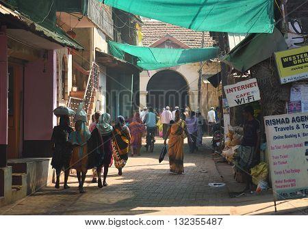 GOKARNA KARNATAKA INDIA - JANUARY 29 2016: Indian woman in yellow traditional indian sari walking down the crowded street in Gokarna city
