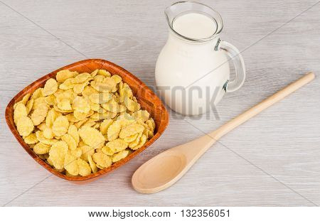 Wooden Bowl With Corn Flakes, Jug Of Milk And Spoon