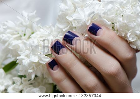Beautiful female hand with purple nail design and white flowers.