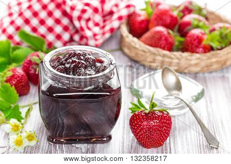 strawberry jam in a jar and fresh berries