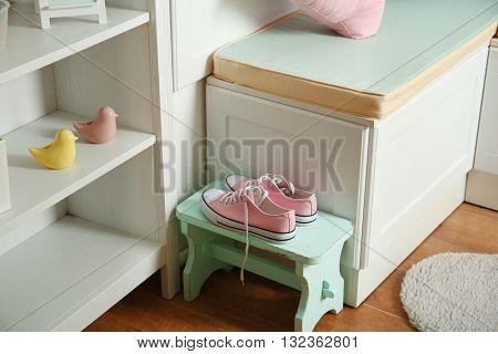 Pink female sneakers beside nook furniture