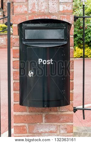 Black post box on a brick wall