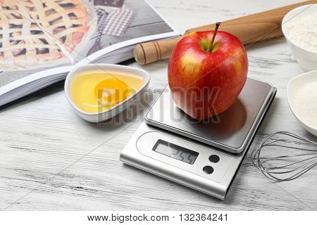 Apple with digital kitchen scales on wooden table. Cooking apple cake concept