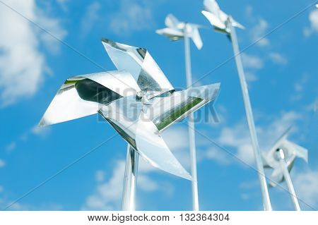 metal pinwheels on background blue sky. silver pinwheel spinning in the wind against cloudy sky