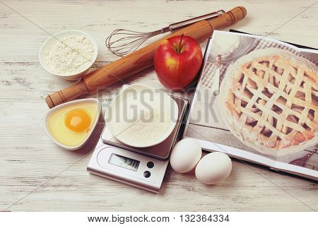 Sugar with digital kitchen scales on wooden table. Cooking apple cake concept