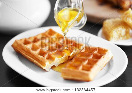 Pouring honey on waffles