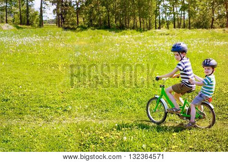 two boys riding on a bicycle. elder brother carries his younger brother on the bike on a blossoming meadow. copy space for your text