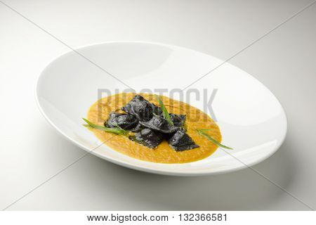 Isolated Pasta dish blacks ravioli stuffed with stockfish