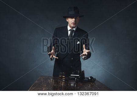 Gesturing And Speaking Vintage 1940 Businessman. Standing Behind Wooden Table.