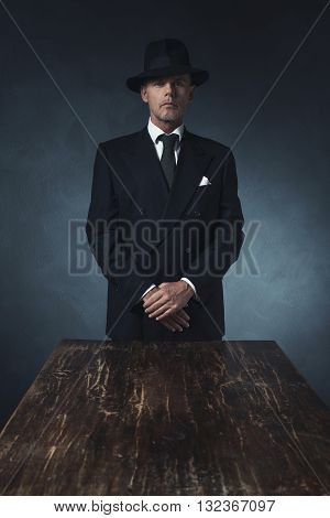 Bossy Vintage 1940 Businessman Standing Behind Wooden Table.