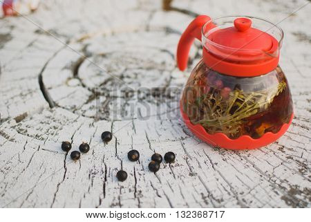 teapot of fruit tea with herbs and blackcurrant berry on the white tree stump.
