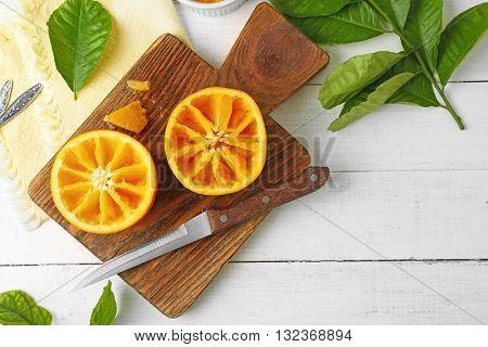 Halved juicy orange on wooden board