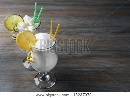 Hurricane glasses with granulated sugar on wooden table