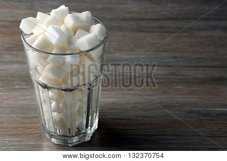 Highball glass with lump sugar on wooden table