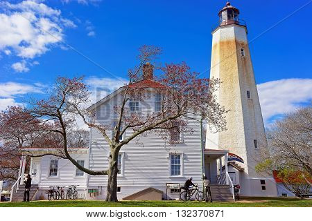 Middletown Township USA - April 26 2015: Sandy Hook Light tower and house building. Sandy Hook is located in Highlands in Monmouth County of New Jersey USA. Tourists nearby