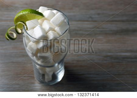 Glass with lump sugar on wooden table