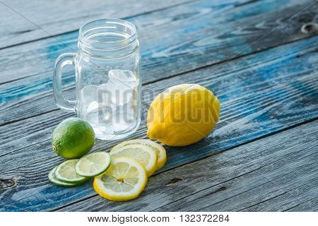Glass Jar And Melted Ice Cubes With Citrus Fruits On A Rustic Wooden Board