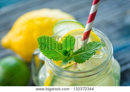 Jug With Lemon And Lime Infused Water On A Rustic Wooden Surface