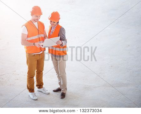 Planning. Cheerful and smiling builders standing together, looking at laptop with apprentices and talking