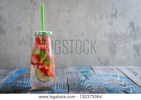Bottle With Lime And Strawberry Infused Water On A Rustic Wooden Surface