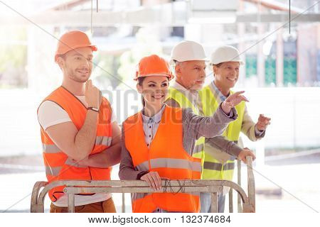 Future strategy. Positive and cheerful businesswoman and businessman standing and talking about future and standing near a pair of businessmen standing together in a background