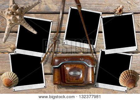 Vintage camera with leather case and five empty instant photo frames on a wooden boardwalk with sand seashells and a starfish