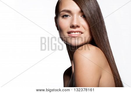Young woman with smooth shiny dark hair and bare shoulders on a white background