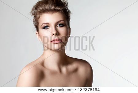 Portrait of an elegant woman with a beautiful hair and evening with natural make-up in a dress with bare shoulders