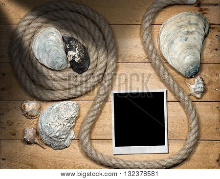 One empty instant photo on a wooden background with an old rope and seashells