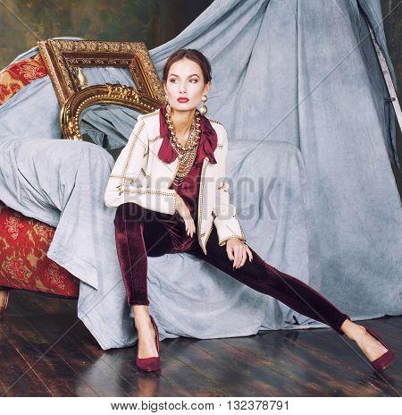 beauty rich brunette woman in luxury interior near empty frames, vintage elegance, gold close up