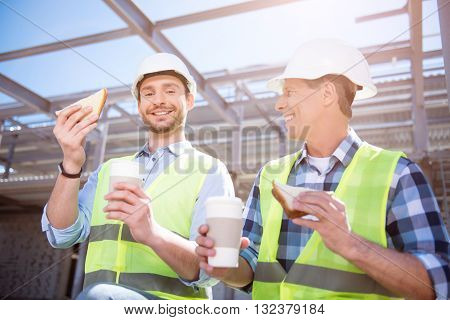 Lunch-hour.  Smiling and very positive workers having meal break and holding cups of nice coffee and tasty sandwiches while being on construction