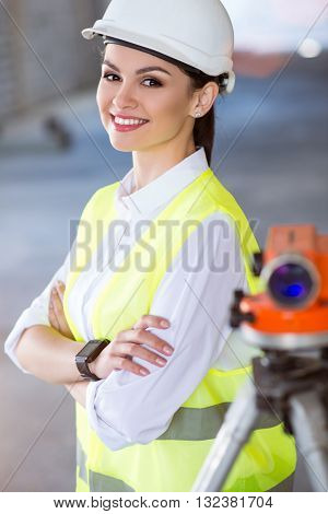 Construction place. Positive and delighted young architect standing near a geodetic level and looking at a camera