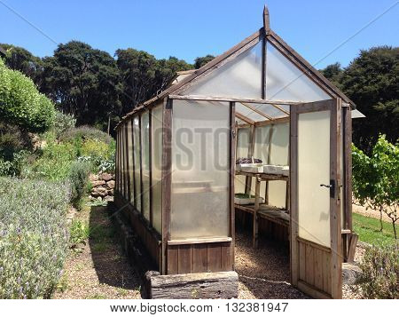 Wooden greenhouse in a garden - landscape orientation