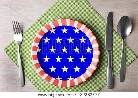 Plate with silver cutlery and napkin on wooden table, top view. American cuisine food concept