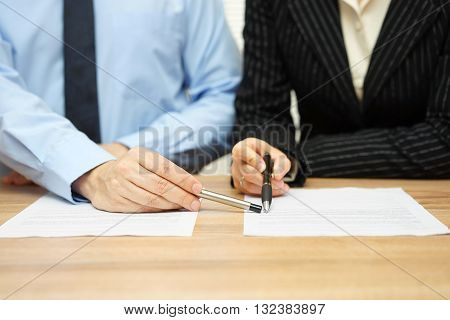 Business people discussing about contract manager pointing on content in document