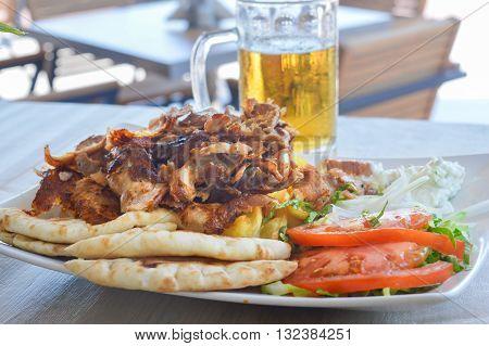 Pork Gyros On A Plate With Salad And A Bear