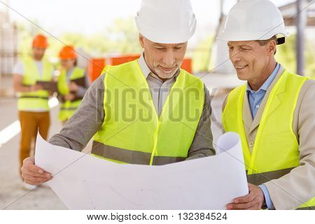 Professional behavior. Cheerful and confident pair of architects standing and looking at a construction plan with another pleasant pair of architects in a background
