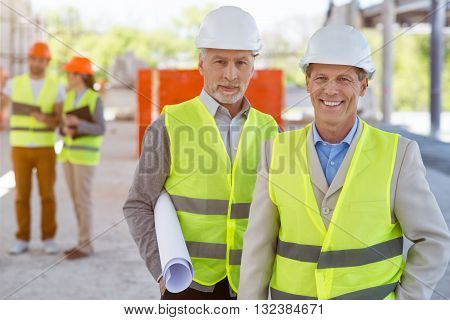 Being in a good mood. Cheerful and positive pair of architects standing and looking at a camera while holding a construction plan with a pair of another architects in a background