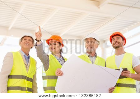 Working steps.  Positive and smiling female architect standing and poking somewhere for her cheerful colleagues while showing and talking about new construction
