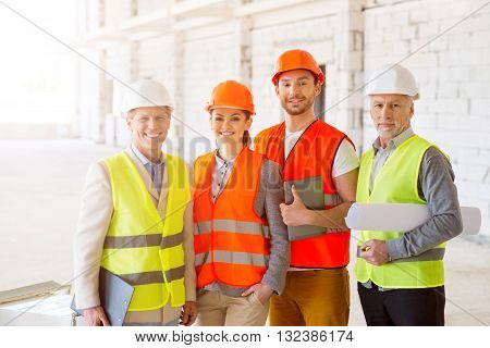 Smiling team. Cheerful and content group of architects and engineers standing together near a new undone high building and holding construction plans, papers and a digital tablet