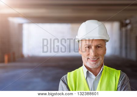 Sincere smile.  Cheerful and positive man in helmet standing in a new building and being in a very good mood