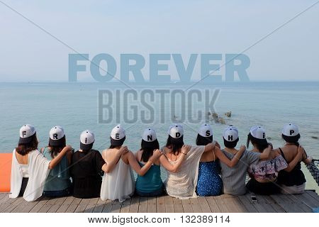 women friend group sit make arm hug hold around their friend's shoulder on wooden pier. They wear same design caps with FRIENDSHIP alphabets on each one.  looking at FOREVER word on blue sea sky.