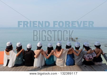 women friend group sit make arm hug hold around their friend's shoulder on wooden pier. They wear same design white and black color caps. looking at FRIEND FOREVER word on blue sea sky.